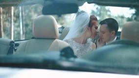 Recienes casados que sientan el descapotable del coche, mirada en uno a, sensaciones de la experiencia de la dulzura metrajes