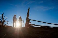 Recienes casados románticos que caminan contra el sol en campo alpino honeymoon foto de archivo libre de regalías