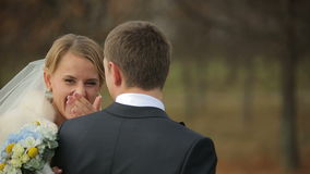 Recienes casados sonrientes de los pares felices de la boda que caminan en parque del otoño almacen de video