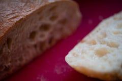 Recientemente pan del ciabatta del corte en tabla de cortar roja foto de archivo