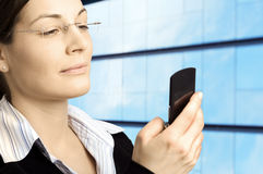 Recieving message. Attractive businesswoman dials on a mobile phone Royalty Free Stock Photos