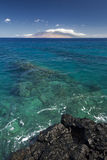 Recife na água clara com vista das montanhas ocidentais de Maui da costa sul São enchidos sempre com os veículos do visitante Foto de Stock Royalty Free