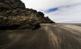 Recife na praia com a areia preta em Karekare Imagem de Stock
