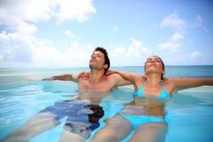Recién casados que se relajan en piscina Imágenes de archivo libres de regalías