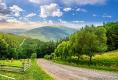 Recinti vicino alla strada giù la collina con la foresta in montagne al sunri Fotografie Stock