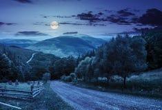 Recinti vicino alla strada giù la collina con la foresta in montagne alla notte Fotografia Stock