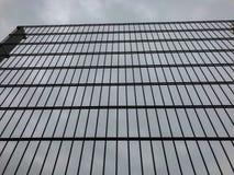 Recinto alto del metallo contro un cielo grigio Confine o concetto della prigione fotografia stock