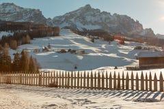 Recinto, Camere e montagne di legno con neve in Europa: Picchi delle alpi delle dolomia per gli sport invernali Immagine Stock Libera da Diritti