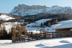 Recinto, Camere e montagne di legno con neve in Europa: Picchi delle alpi delle dolomia per gli sport invernali Fotografia Stock Libera da Diritti