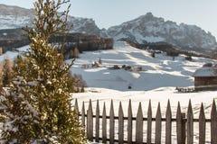 Recinto, Camere e montagne di legno con neve in Europa: Picchi delle alpi delle dolomia per gli sport invernali Immagini Stock Libere da Diritti