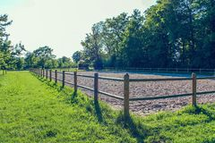 Recinto chiuso della sabbia in parco con il recinto di legno, erba verde, alberi fotografia stock