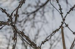 Recinto con filo spinato contro il cielo fotografia stock
