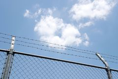 Recinto con i fili spinati su cielo blu fotografia stock