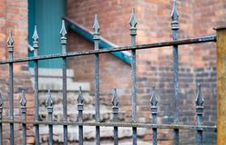 Recinto del ferro battuto con il fondo del muro di mattoni fotografia stock libera da diritti