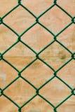 Recinto di filo metallico verde arrugginito con il fondo della parete di lerciume Fotografia Stock