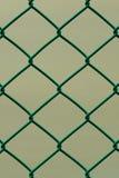 Recinto di filo metallico verde isolato sul fondo di Brown, modello verticale Immagini Stock Libere da Diritti