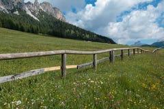 Recinto di legno, pascolo verde e montagne delle alpi delle dolomia nel fondo, Italia Immagine Stock