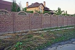 Recinto di pietra rurale di Brown vicino alla casa vicino all'erba Fotografia Stock