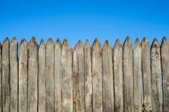 Recinto fatto dei pali di legno taglienti contro il cielo blu I ceppi verticali del recinto di legno hanno indicato contro la pro fotografie stock
