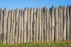 Recinto fatto dei pali di legno taglienti contro il cielo blu I ceppi verticali del recinto di legno hanno indicato contro la pro fotografia stock