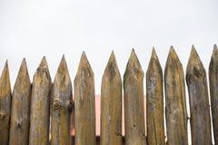 Recinto fatto dei pali di legno taglienti contro il cielo grigio fotografie stock