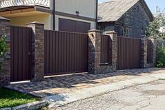Recinto marrone grigio del ferro davanti ad una strada asfaltata Fotografia Stock Libera da Diritti