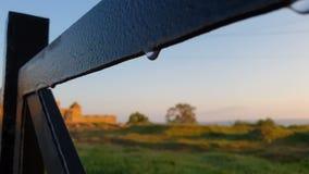 Recinto metallico con le gocce di acqua e di una fortezza alla spiaggia vicina nell'estate archivi video