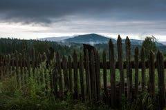 Recinto misero di legno contro un paesaggio della montagna Immagini Stock Libere da Diritti