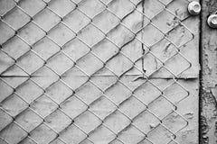 Recinto monocromatico della maglia metallica allegato con una vite alla parete fotografie stock