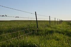 Recinto rustico del filo spinato intorno a terreno agricolo fotografie stock libere da diritti