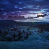 Recinto sul pendio di collina vicino alla foresta in montagna alla luce di luna piena Fotografia Stock