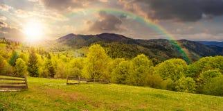 Recinto sul prato del pendio di collina in montagna al tramonto Fotografia Stock