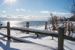 Recinto vicino al lago nell'inverno con il fondo della neve e del cielo blu fotografia stock