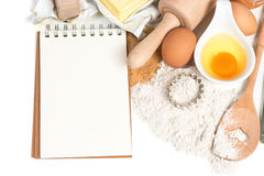 Recipe book and baking ingredients eggs, flour, sugar, butter, y Stock Photography