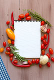 Recipe book with fresh vegetables and herbs on wooden. Stock Image