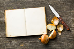 Recipe book and halved onion Stock Photos