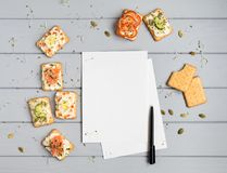 Recipe book page and crackers with cream cheese and various toppings. Appetizers on grey table. Top view, flat lay Royalty Free Stock Image