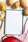 Recipe book with potatoes. On kitchen table Royalty Free Stock Photo