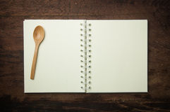 Recipe book and spoon. On wooden table royalty free stock photos