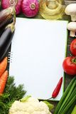 Recipe book with vegetables. Blank recipe book with vegetables on wooden table Royalty Free Stock Photography