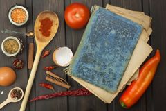 Recipe book and vegetables. Chili pepper and tomatoes. Food preparation according to the old recipe book. stock photos
