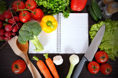 Recipe book. With vegetables and herbs on wooden background Royalty Free Stock Image