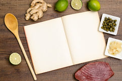 Recipe book with wooden spoon and text space stock photos