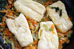 Recipe for cod. Pieces of cod cooked in a pan and flavored with sauce Stock Photography
