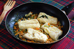 Recipe for cod. Pieces of cod cooked in a pan and flavored with sauce Stock Image