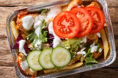 Recipe Dutch fast food kapsalon of french fries, chicken, fresh. Salad, cheese and sauce close-up in a foil tray on the table. horizontal top view from above royalty free stock photography