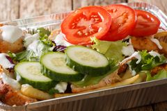 Recipe Dutch fast food kapsalon of french fries, chicken, fresh. Salad, cheese and sauce close-up in a foil tray on the table. horizontal stock image