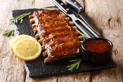 Recipe fried pork ribs with spicy sauce, rosemary and lemon close-up. horizontal stock photography
