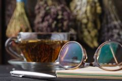 Recipe of healing herbal tea with open notebook Royalty Free Stock Photo