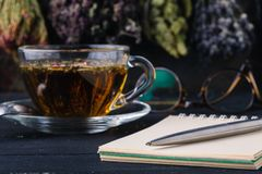 Recipe of healing herbal tea with open notebook Stock Images